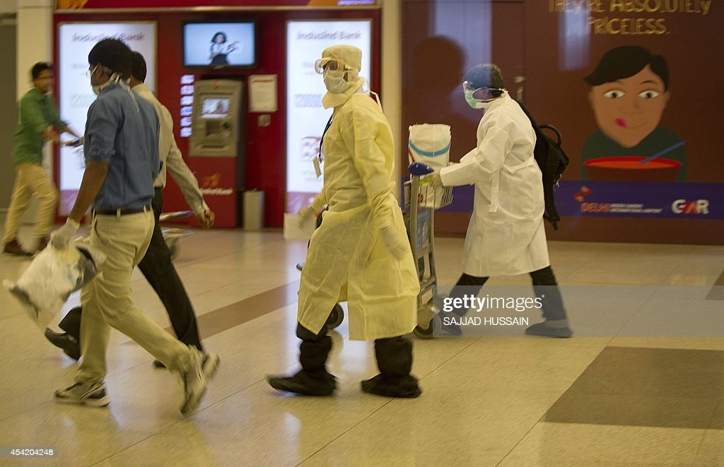 A traveller, who was not cleared after being screened for the Ebola virus on his arrival in India, walks towards an ambulance at the International airport in New Delhi on August 26, 2104. Thirteen Indian nationals, who arrived in Delhi from Liberia on August 26, have been cleared after being screened for the Ebola virus, Health Ministry said.