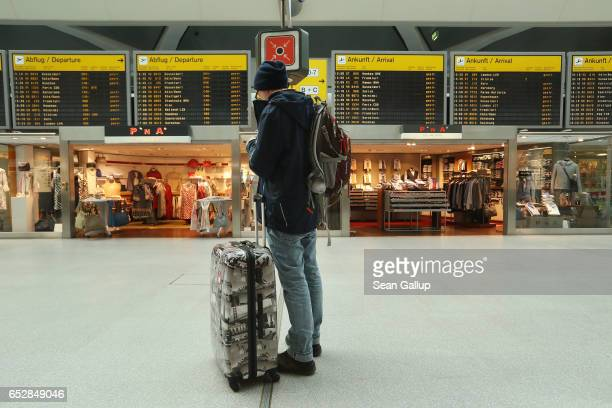 A traveller whose flight to Moscow was cancelled checks his mobile phone under an arrival and departures baord during a strike by ground personnel at...