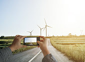 Traveller woman taking pictures with smartphone from personal point of view of the Windmills On Grassy Field Against Sky