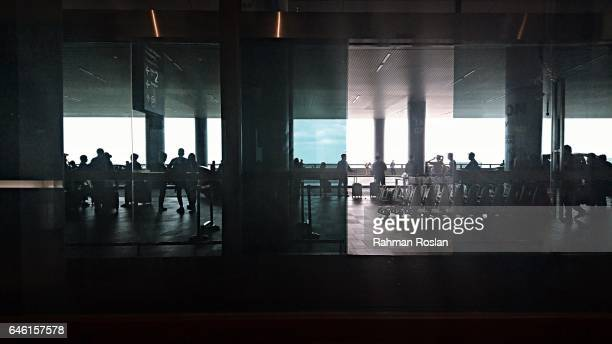 Travellers are seen in front of the exit where one of Kim Jong Nam's attacker are believed to board a taxi after the attack happens in Kuala Lumpur...