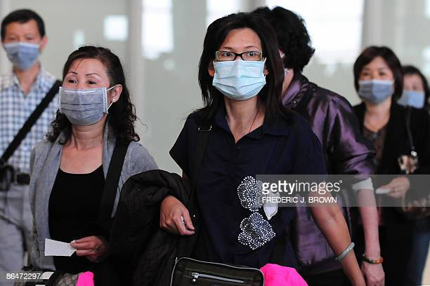 Travellers arrive wearing protective facemasks at Beijing airport on May 7 2009 as China started lifting a sevenday quarantine on passengers who had...