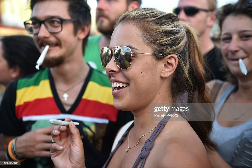 Travellers at the Mardi Grass festival smoke during the Global Marijuana March in the eastern Australian town of Nimbin on April 30, 2016. . The festival, an annual cannabis law reform protest and gathering, attracts thousands of revellers from across Australia and around the world. / AFP / PETER