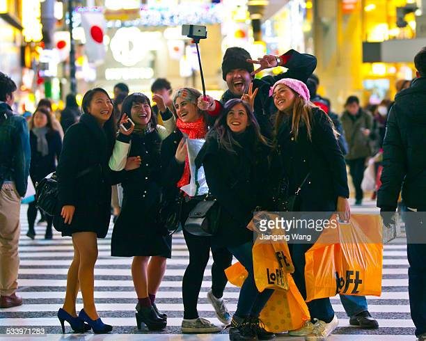Travellers from abroad take photo with mobile phone camera using a selfie stick at the famous Shibuya scramble crossing Some local people also join...