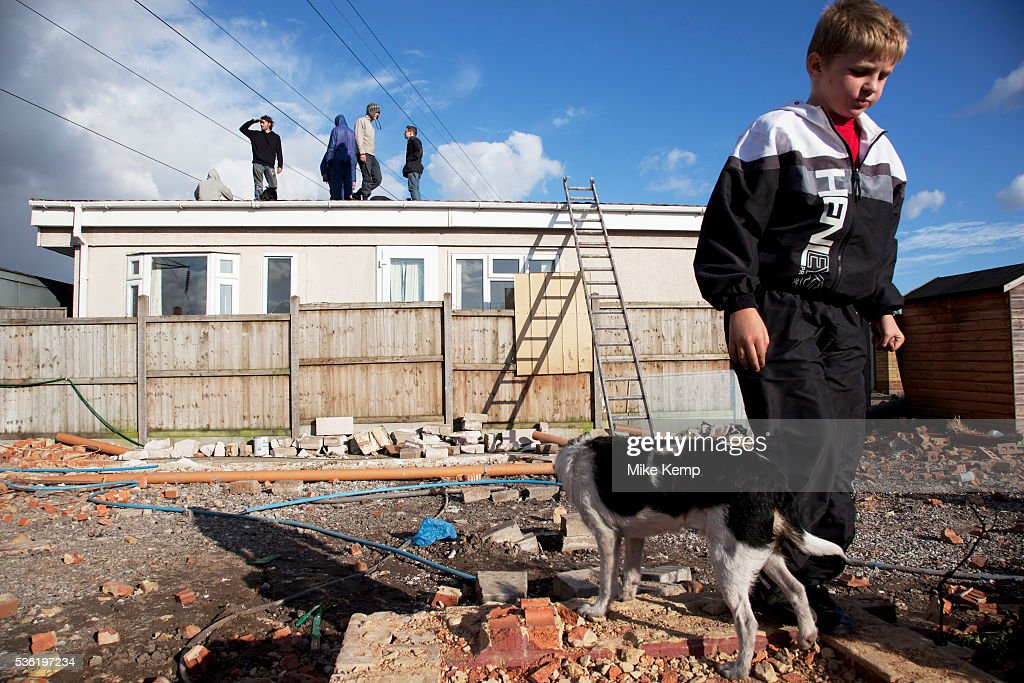 Travellers look on from a roof of one of their homes as the situation develops Protesters who barricaded themselves above the entrance to the Dale...