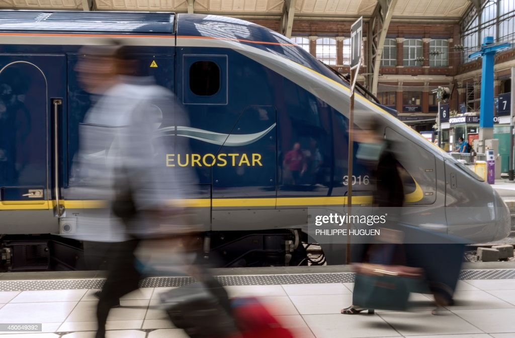 Travellers pass by an Eurostar train at Lille's train station northern France on June 13 on the third day of a national strike by French SNCF railway...
