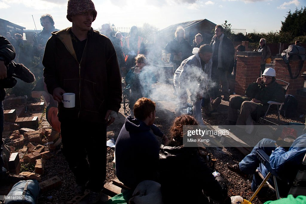Travellers sit around a fire chatting and waiting for developments at Dale Farm site prior to eviction Riot police and bailiffs were present on 20th...