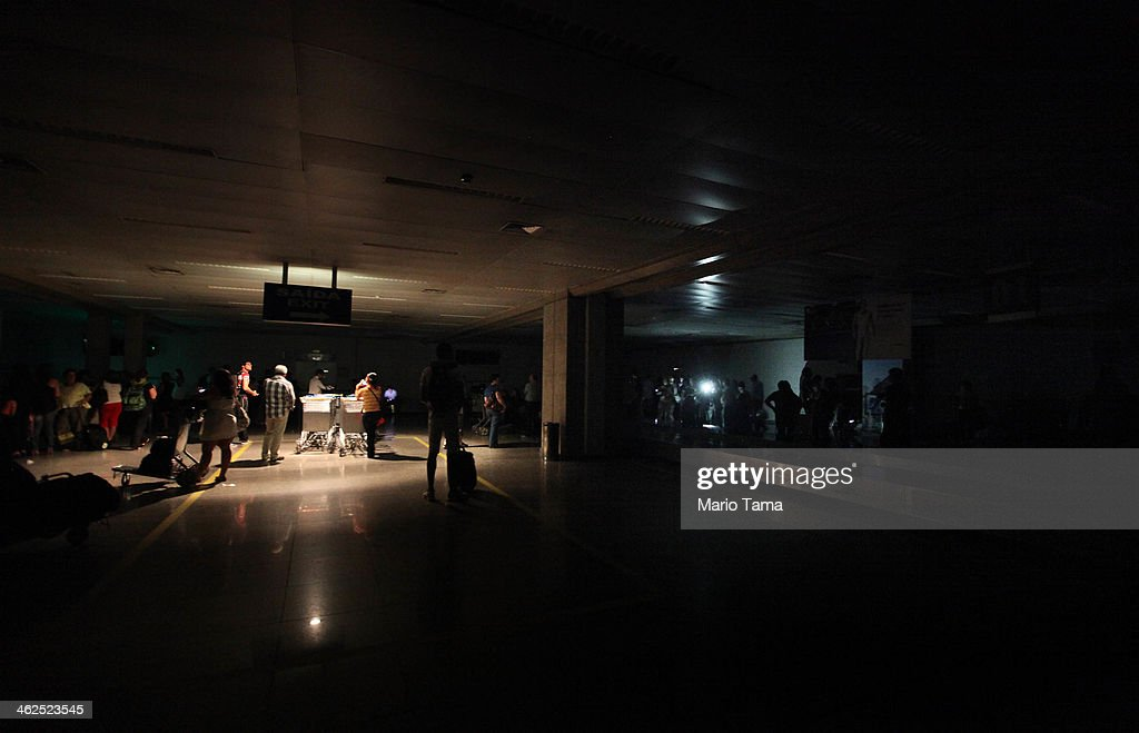 Travellers stand in the dark in the baggage claim area beneath one emergency light as another person shines a flashlight during an approximately ten-minute power outage at Carlos Jobim International Airport on January 13, 2014 in Rio de Janeiro, Brazil. The airport sustained three brief power outages today according to airport workers. Brazil's airports are a concern with 500,000 foreign visitors expected for the World Cup.