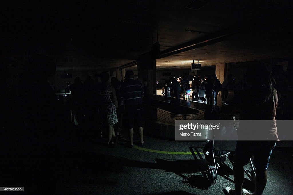 Travellers stand in the dark in the baggage claim area beneath one emergency light during an approximately ten-minute power outage at Carlos Jobim International Airport on January 13, 2014 in Rio de Janeiro, Brazil. The airport sustained three brief power outages today according to airport workers. Brazil's airports are a concern with 500,000 foreign visitors expected for the World Cup.