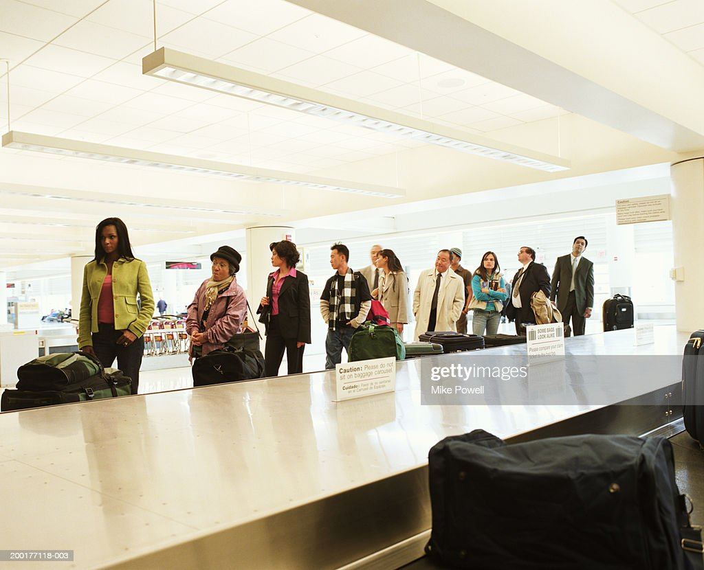 Travellers standing by airport luggage carousel : Stock Photo