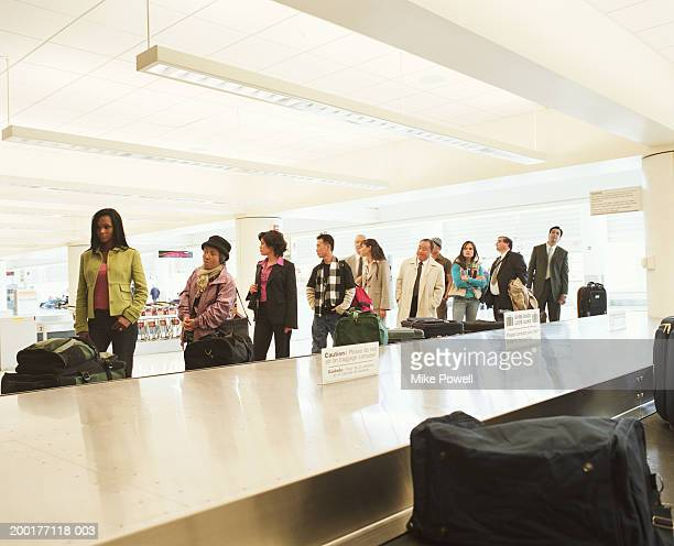 Travellers standing by airport luggage carousel