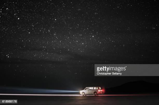Travellers van on desert under starry sky