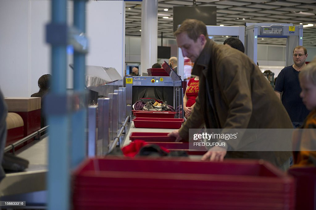 Travellers wait for security check at the Charles de Gaulle airport on December 31, 2012 in Roissy.