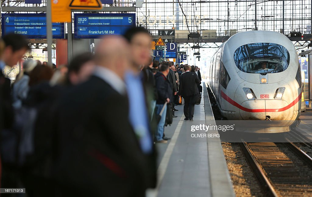 Travellers wait for the train at a railway station in Cologne, western Germany, on April 22, 2013, during a warning strike of ground staff of German airline Lufthansa. German airline Lufthansa said it has cancelled most of its domestic, European and long-haul flights at six German airports due to strike action by ground personnel and some cabin crew. AFP PHOTO / OLIVER BERG / GERMANY OUT