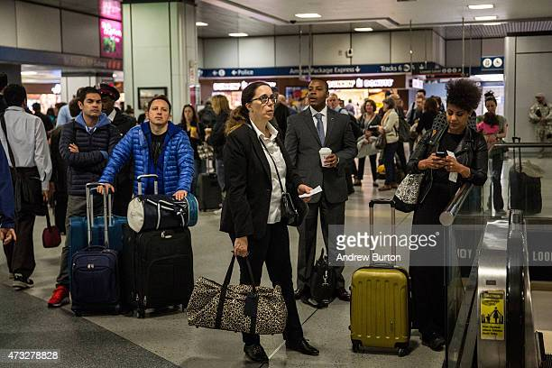 Travellers wait for train information in the Amtrak terminal of New York Penn Station on May 14 2015 in New York City An Amtrak crash on Tuesday...
