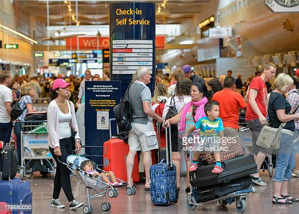 Travellers wait in the terminal building at Stockholm's Arlanda airport after landings and takeoffs were halted on August 17 2013 in Stockholm A...