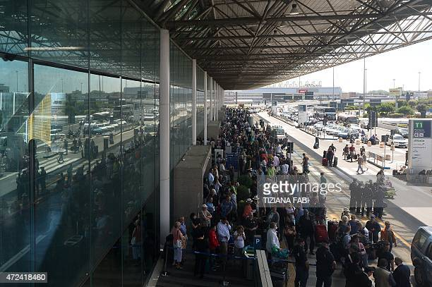 Travellers wait outside Rome's Fiumicino international airport where a fire broke out overnight at Terminal 3 on May 7 2015 Several airport employees...