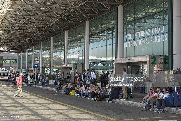 Travellers wait outside the Fiumicino International Airport after a fire broke out overnight on May 07 2015 Rome's main airport gradually resumed...