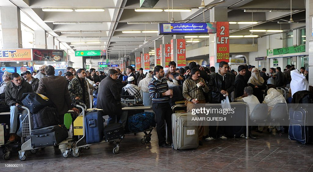 Travellers wait outside the International departure lounge of the Benazir Bhutto International Airport during a strike by employees of the flagship...