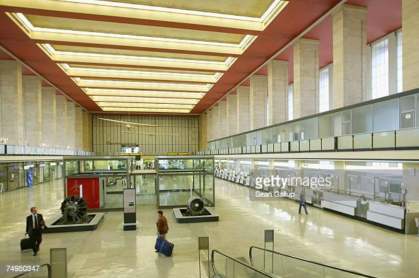 Travellers walk through the main hall at Tempelhof Airport June 29 2007 in Berlin Germany Tempelhof Airport first built in 1923 and extended into its...