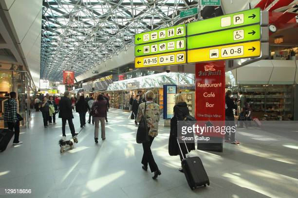 Travellers walk through the main terminal at Tegel Airport on October 17 2011 in Berlin Germany Tegel which first went into operation in 1960 and...