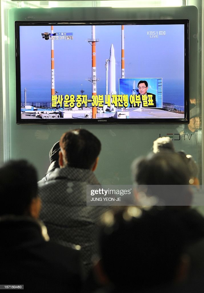 Travellers watch a TV screen broadcasting live footage on South Korea's third attempt of a rocket launch, at a railway station in Seoul on November 29, 2012. South Korean space officials halted the countdown on a crucial rocket launch, aimed at placing a satellite in orbit and announcing the country's entry into an elite global space club. AFP PHOTO / JUNG YEON-JE
