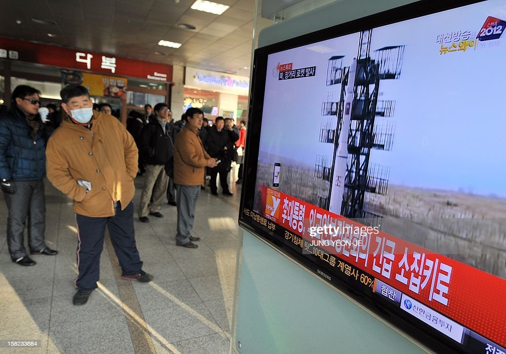 Travellers watch a TV screen broadcasting news about North Korea's rocket launch, at a railway station in Seoul on December 12, 2012. North Korea on December 12 launched a long-range rocket which Japanese authorities said passed over its southern island chain of Okinawa. It was the second launch this year, after a failed attempt in April.