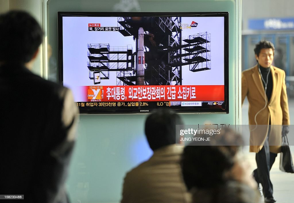 Travellers watch a TV screen broadcasting news on North Korea's rocket launch, at a railway station in Seoul on December 12, 2012. North Korea on December 12 launched a long-range rocket which Japanese authorities said passed over its southern island chain of Okinawa. It was the second launch this year, after a failed attempt in April. AFP PHOTO / JUNG YEON-JE