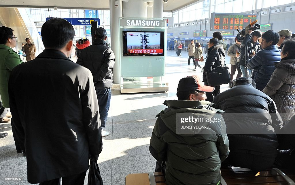 Travellers watch a TV screen broadcasting news on North Korea's rocket launch, at a railway station in Seoul on December 12, 2012. North Korea on December 12 launched a long-range rocket which Japanese authorities said passed over its southern island chain of Okinawa. It was the second launch this year, after a failed attempt in April.