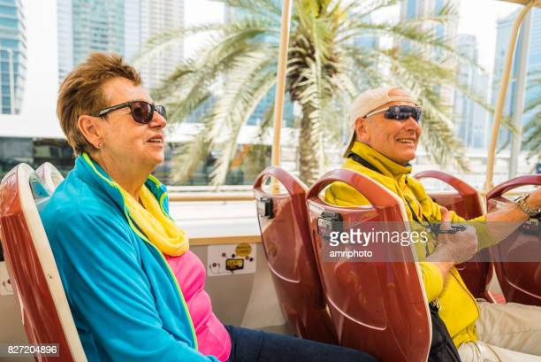 Travelling to Middle East, couple in sightseeing bus in Dubai on unusually cool day