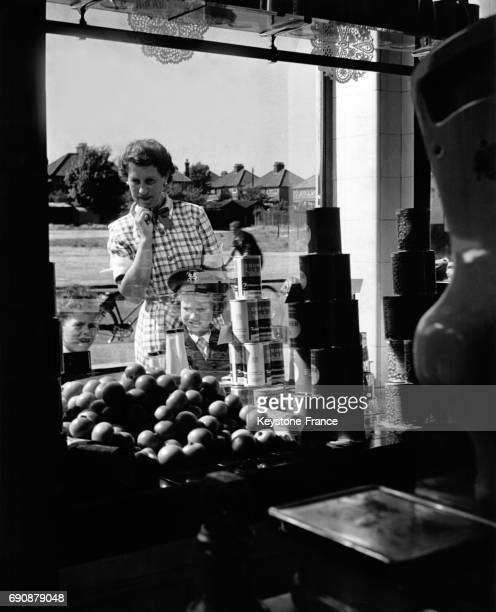 A travers la vitrine d'un magasin d'alimentation une femme et son enfant regardent le prix des fruits au RoyaumeUni