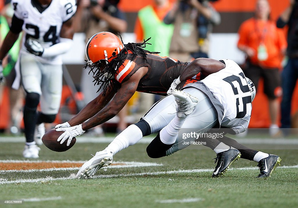 Travis Benjamin of the Cleveland Browns dives for a touchdown in front of DJ Hayden of the Oakland Raiders during the fourth quarter at FirstEnergy...