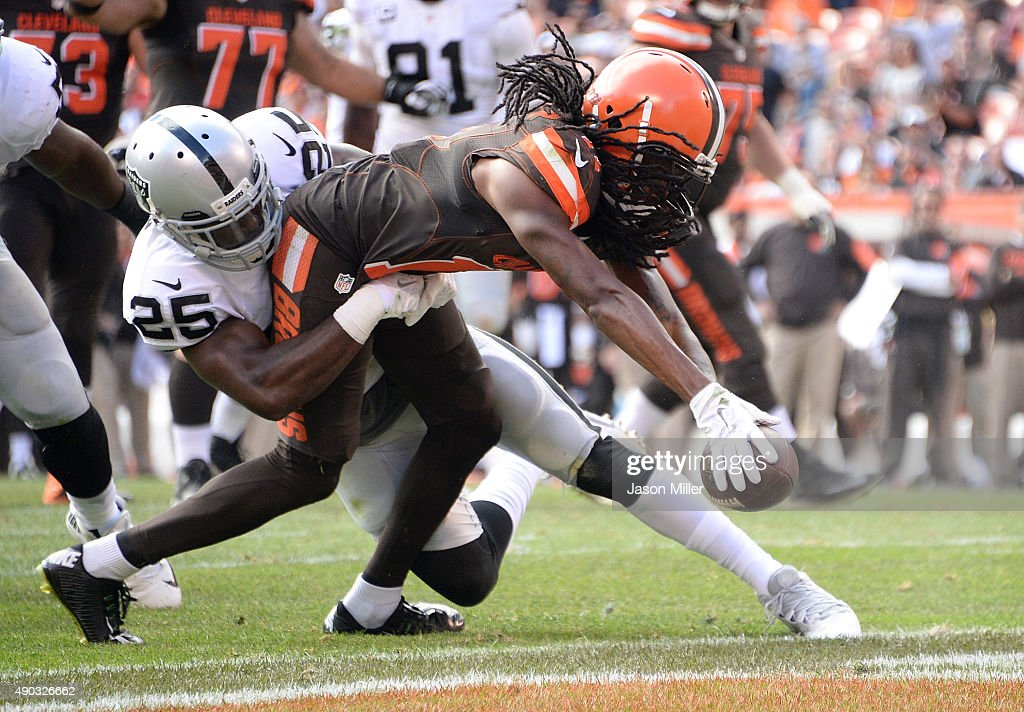 Travis Benjamin of the Cleveland Browns dives for a touchdown while being tackled by DJ Hayden of the Oakland Raiders during the fourth quarter at...
