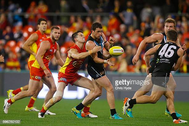 Travis Boak of the Power handballs during the round 23 AFL match between the Gold Coast Suns and the Port Adelaide Power at Metricon Stadium on...