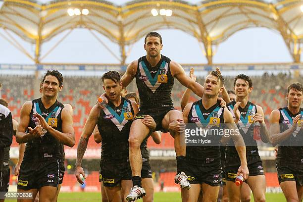 Travis Boak of the Power is chaired from the field after playing his 150th game during the round 21 AFL match between the Gold Coast Suns and the...