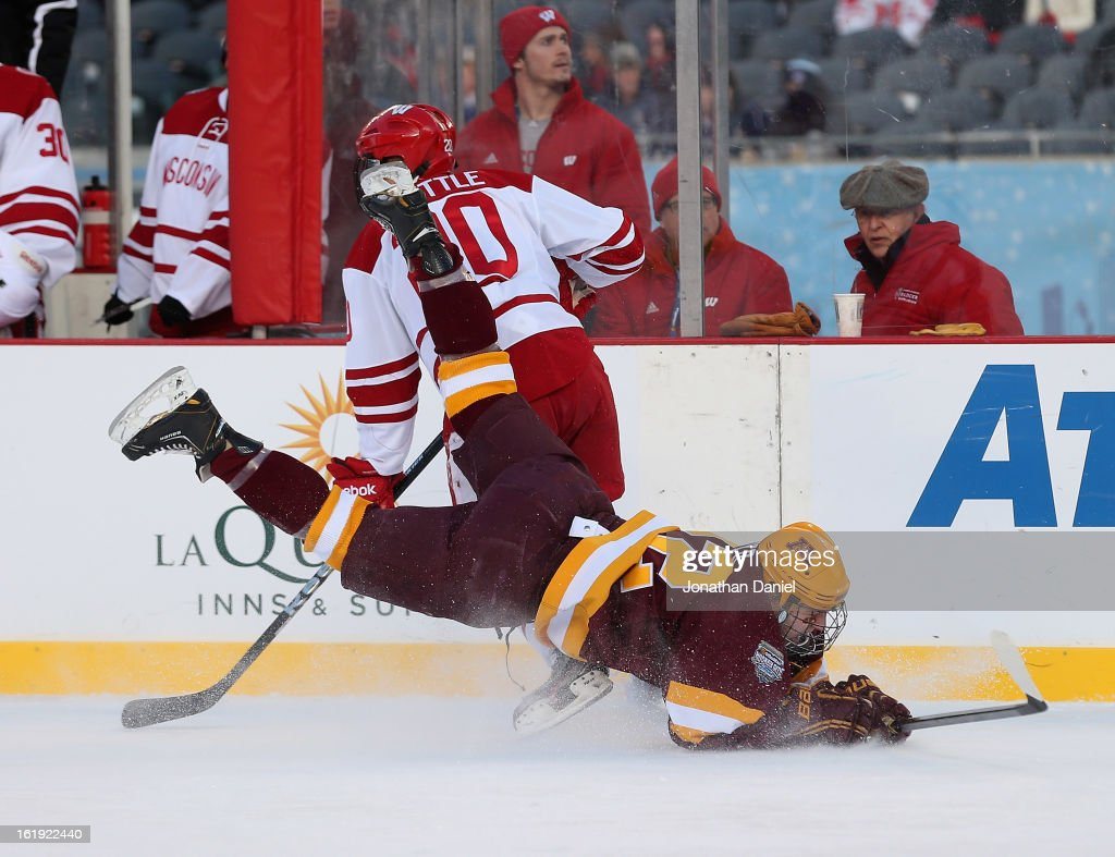 Travis Boyd #22 of the Minnesota Golden Gophers hits the ice after colliding with Ryan Little #20 of the Wisconsin Badgers during the Hockey City Classic at Soldier Field on February 17, 2013 in Chicago, Illinois.