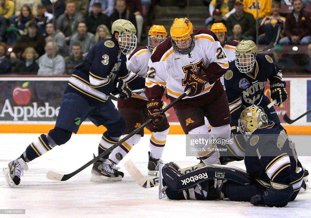 Travis Boyd #22 of the Minnesota Gophers battles for a bouncing puck as Shayne Taker #3 and Steven Summerhays #1 of the Notre Dame Fighting Irish look on January 8, 2013 at Mariucci Arena in Minneapolis, Minnesota.