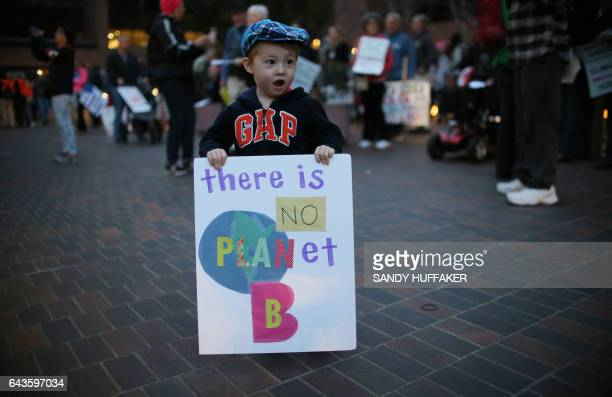 Travis Caballero holds a sign during a rally against climate change in San Diego California on February 21 2017 The US Senate confirmed fossilfuel...