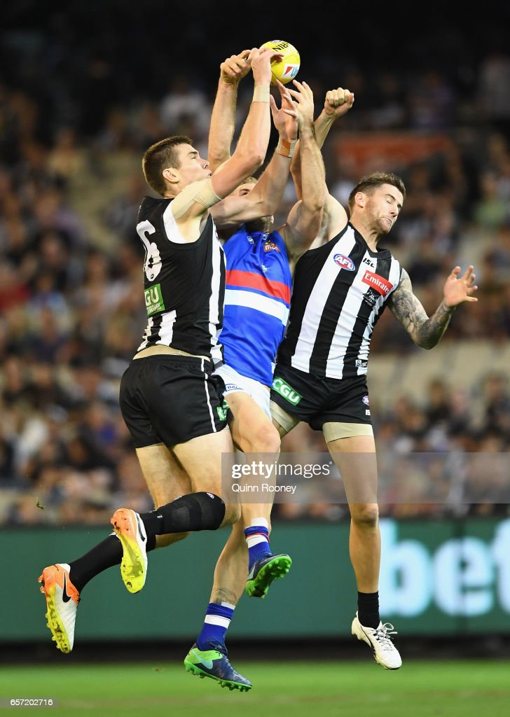 Travis Cloke of the Bulldogs marks in between Mason Cox and Jeremy Howe of the Magpies during the round one AFL match between the Collingwood Magpies and the Western Bulldogs at Melbourne Cricket Ground on March 24, 2017 in Melbourne, Australia.