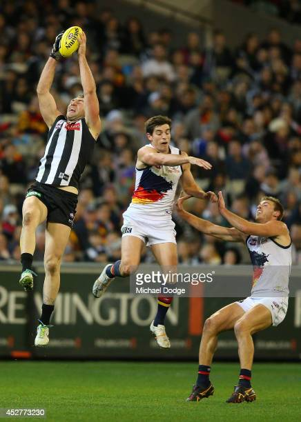 Travis Cloke of the Magpies marks the ball against Ricky Henderson and Daniel Talia of the Crows during the round 18 AFL match between the...