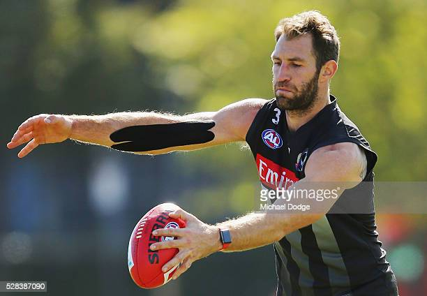 Travis Cloke of the Magpies relegated to the reserves for the past two weeks kicks the ball with a strapped up arm during a Collingwood Magpies AFL...