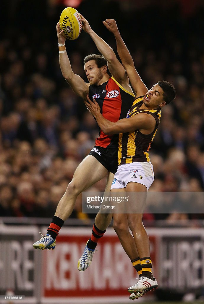 Travis Colyer of the Bombers marks the ball against Bradley Hill of the Hawks during the round 18 AFL match between the Essendon Bombers and the Hawthorn Hawks at Etihad Stadium on July 26, 2013 in Melbourne, Australia.