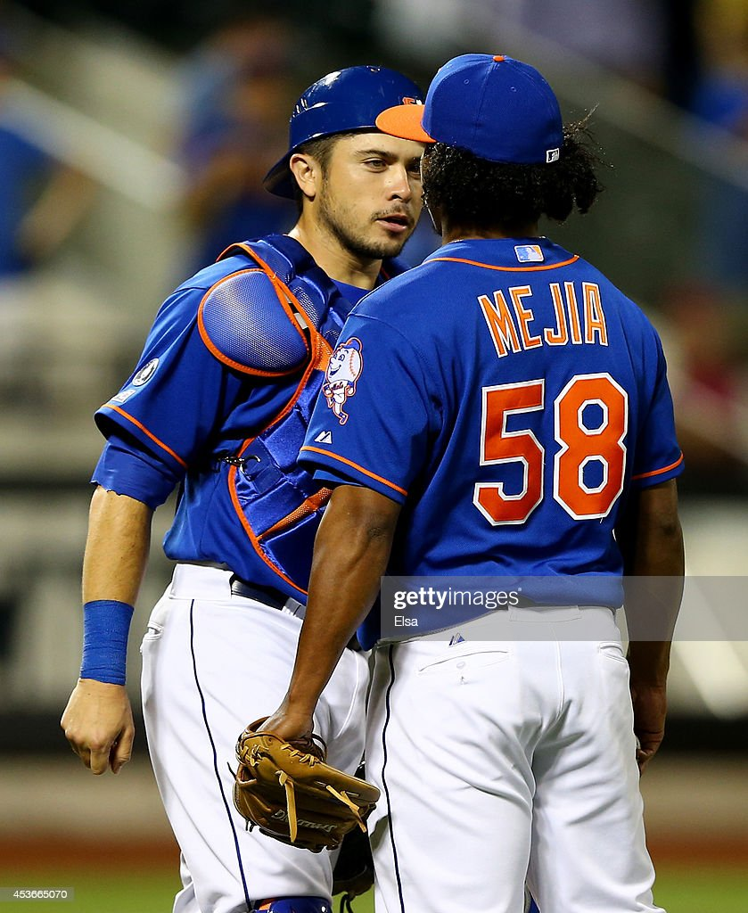 Travis d'Arnaud #15 and Jenrry Mejia #58 of the New York Mets celebrate the 3-2 win over the Chicago Cubs on August 15, 2014 at Citi Field in the Flushing neighborhood of the Queens borough of New York City.