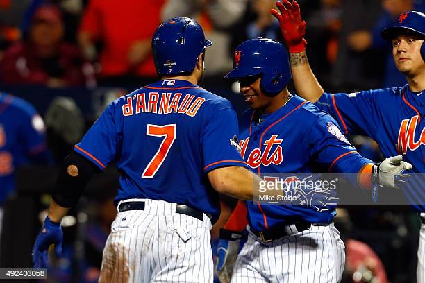 Travis d'Arnaud of the New York Mets celebrates with Yoenis Cespedes after hitting a two run home run in the third inning against Brett Anderson of...