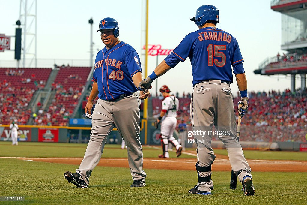 Travis d'Arnaud #15 of the New York Mets congratulates Bartolo Colon #40 of the New York Mets after scoring a run during the second inning against the Cincinnati Reds at Great American Ball Park on September 5, 2014 in Cincinnati, Ohio.