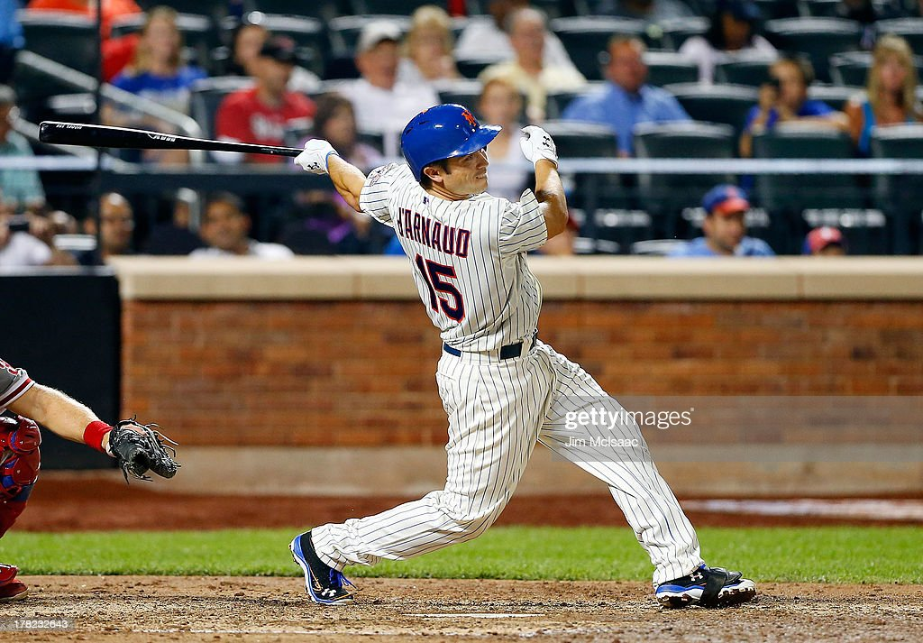 Travis d'Arnaud #15 of the New York Mets follows through on a sixth inning run scoring sacrifice fly against the Philadelphia Phillies at Citi Field on August 27, 2013 in the Flushing neighborhood of the Queens borough of New York City.