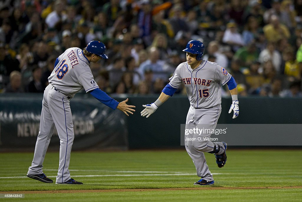 Travis d'Arnaud #15 of the New York Mets is congratulated by third base coach Tim Teufel #18 after hitting a home run against the Oakland Athletics during the fourth inning of an interleague game at O.co Coliseum on August 19, 2014 in Oakland, California.