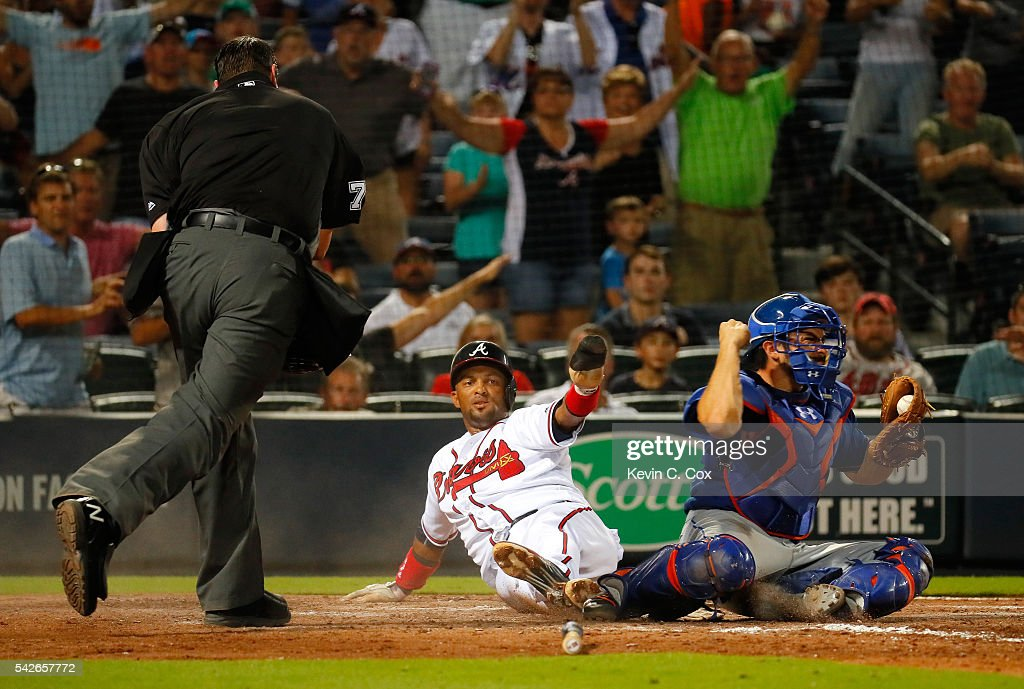 Travis d'Arnaud of the New York Mets reacts as homeplate umpire Jordan Baker calls out Emilio Bonifacio of the Atlanta Braves to end the seventh...