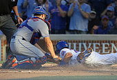 Travis d'Arnaud of the New York Mets tags out Willson Contreras of the Chicago Cubs in the 3rd inning at Wrigley Field on July 16 2016 in Chicago...