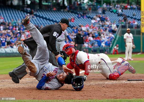 Travis d'Arnaud of the New York Mets tumbles after scoring before the tag of catcher Cameron Rupp of the Philadelphia Phillies on a double by Jose...