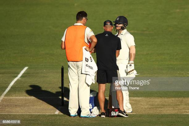 Travis Dean of the Bushrangers receives treatment after being hit on the thumb during the Sheffield Shield final between Victoria and South Australia...